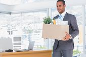 pic of forlorn  - Sad businessman leaving his company while he is holding a box - JPG
