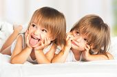 stock photo of pajamas  - happy little girls twins sister in bed under the blanket having fun smiling - JPG