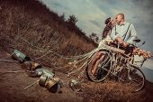 stock photo of marriage decoration  - Groom and bride on a bicycle with just married sign and cans attached - JPG
