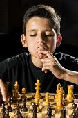 stock photo of 11 year old  - An 11 year old boy thinking about his next move during a chess game - JPG