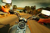 stock photo of driver  - Driver riding motorcycle on an asphalt road in a tropics - JPG