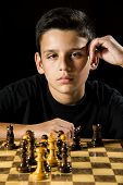 image of 11 year old  - A serious looking 11 year old boy staring down his opponent during a game a chess - JPG