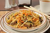 pic of lo mein  - Closeup of a cup of beef lo mein with a cup of tea