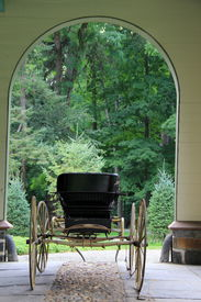picture of entryway  - Old fashioned horse drawn buggy with soft leather seats and big wooden wheels under cover of arched entryway of home - JPG