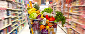 stock photo of grocery cart  - Full shopping grocery cart in supermarket - JPG