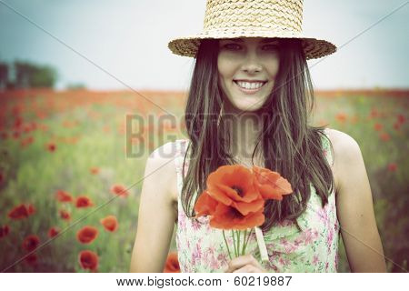 Young beautiful happy woman in straw hat on a poppy field, summer outdoor.