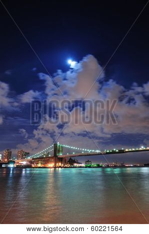 Brooklyn Bridge over East River at night with moon in New York City Manhattan with lights and reflections.
