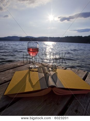 Glass of red wine, book, and sunglasses on dock at lake