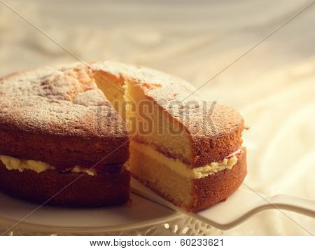 Slicing a Victoria sponge cake revealing the jam and buttercream filling
