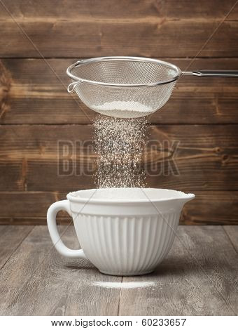 Sifting flour into  a white mixing bowl in the kitchen