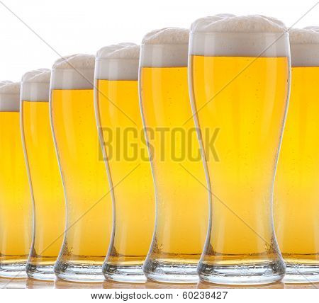 Closeup Glasses of Foamy Beer on a white background. The glasses have condensation and reflections in the table top.