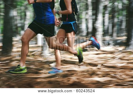Couple running fast through the forest on trail run with motion blur