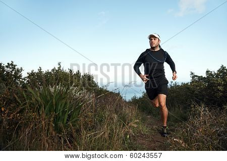 fitness running man on mountainn trail near ocean exercising for marathon training