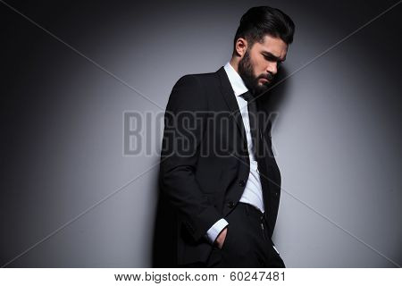 side view photo of a young fashion man holding his hands in his pockets and looking down, away from the camera with a sad expression. on a dark background