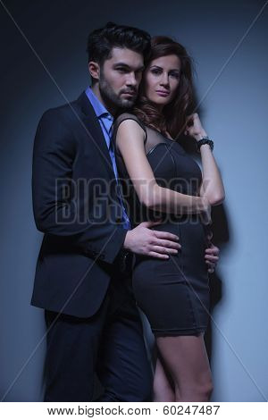 portrait of a young fashion couple where the man holds the woman from behind and looks away over her shoulder and she is looking into the camera. on a dark blue background