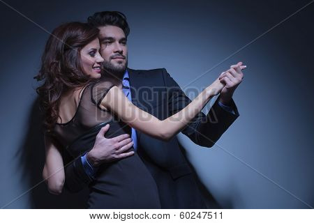 portrait of a young fashion couple dancing while looking away from the camera. on a dark blue background