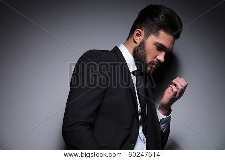 closeup portrait of a young fashion man looking at his nails. on a dark background