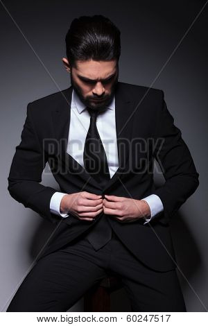 young business man sitting on a chair and buttoning his suit jacket while looking down, away from the camera. on a dark background