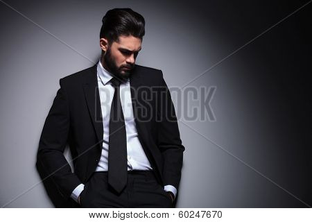 front portrait of a young bearded fashion man standing against a wall with his hands in his pockets and  looking down, away from the camera. on a dark background