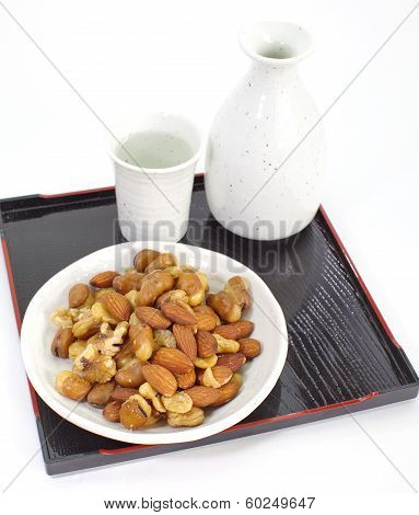 mix nuts with japanese sake bottle and white sake cup on background