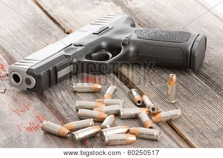 Handgun And Bullets Lying On A Wooden Table