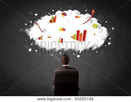 Young businessman sitting in an office chair with colorful charts in a cloud above his head