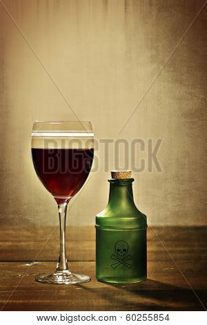 glass red wine with poison bottle