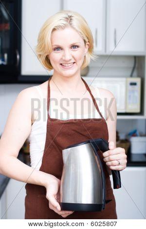 hervidor de explotación de mujer en la cocina
