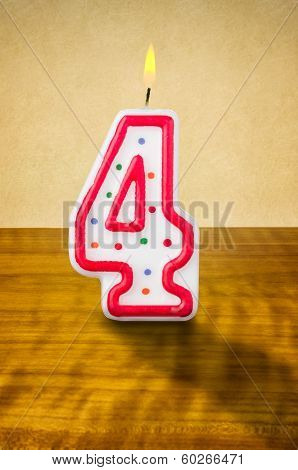 Burning birthday candle number 4 on a wooden background