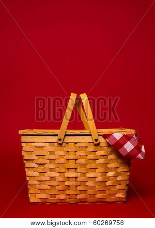 A brown, wicker picnic basket with red gingham tablecloth on a red background with copy space