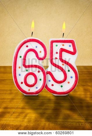 Burning birthday candles number 65 on a wooden background