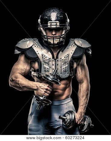 American football player with dumbbells wearing helmet and protective armour
