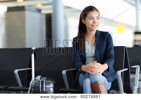 Passenger. Asian woman in airport waiting for air travel. Young business woman smiling sitting with travel suitcase trolley, in the waiting hall of the departure lounge of an international airport.