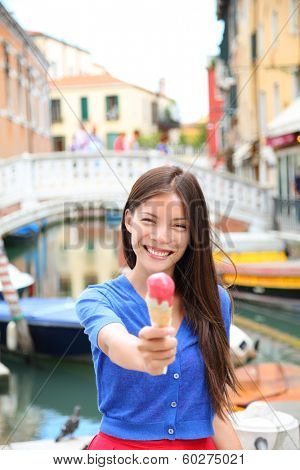 Ice cream eating woman in Venice, Italy on vacation travel showing gelato ice cream cone smiling happy looking at camera. Tourist having fun eating italian food on holidays in Venice, Italy, Europe.