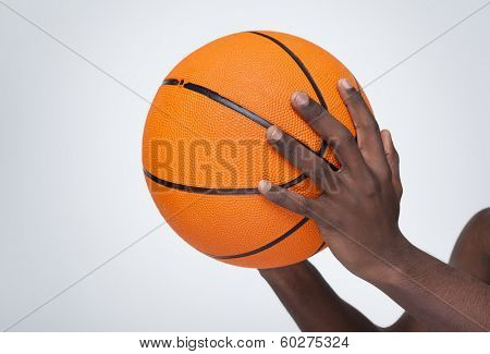 Basketball player holding a ball against gray background