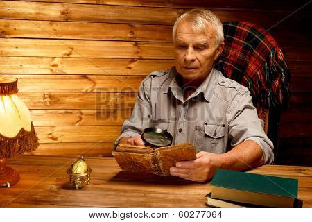 Senior man with magnifier reading vintage book in homely wooden interior