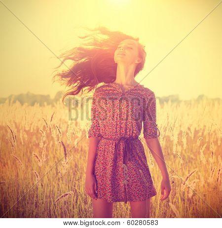 Beauty Romantic Girl Outdoors. Beautiful Teenage Model girl in Casual Short Dress on the Field in Sun Light. Blowing Long Hair. Autumn. Glow Sun, Sunshine. Backlit. Toned in warm colors