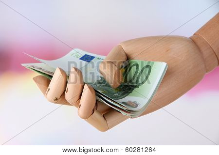 Money in wooden hand, on light background