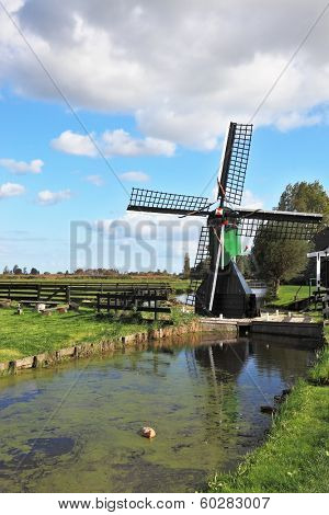 The village - an ethnographic museum in Holland. The picturesque windmill  is reflected in the channel