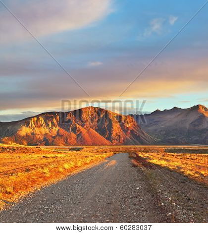 Argentina Patagonia. Perito Moreno's huge and magnificent national park. The gravel road between boundless Pampas. The sunset sun shines mountains and the steppe with red light