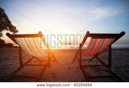 Loungers on the deserted coast sea at sunrise.