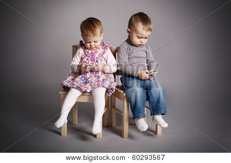 boy and girl playing with mobile phones