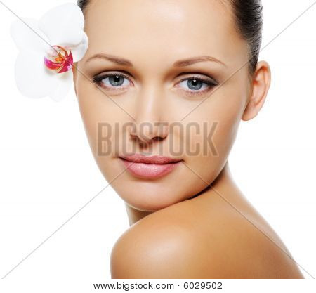 Woman With  Clear Skin And Flower Near Her Eyes