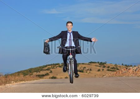 Carefree businessman holding a  briefcase and riding a bicycle