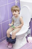 picture of defecate  - Cute smiling baby on toilet drawing himself - JPG