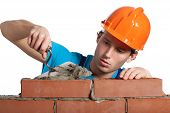 image of bricklayer  - A bricklayer putting bricks being very concentrated - JPG