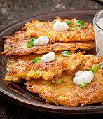 foto of frizzle  - Fried potato pancakes on the old wooden background - JPG