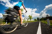 Female cyclist biking on a country road on a lovely sunny day (motion blurred image with copy space)