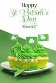 picture of irish flag  - Happy St Patricks Day green cupcakes with shamrock flags on green and white background with sample text or copy space for your text here - JPG