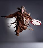 stock photo of shaman  - Studio shot of angry shaman posing in jump, on gray background